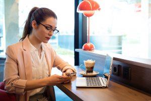 Nainen juo kahvia ja lyö vetoa puhelimella kahvilassa